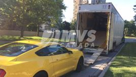 Mustang being loaded into the enclosed car shipping trailer