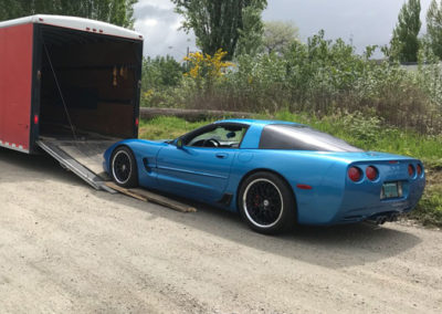 Blue Chevrolet Corvette driving up low angle ramp into trailer