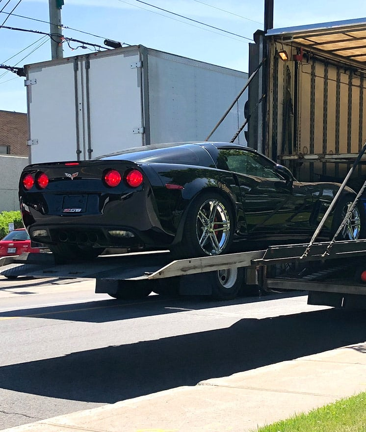 Chevrolet Corvette loaded into enclosed trailer using hydraulic lift gate