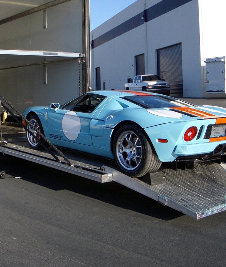 Ford GT being loaded into an enclosed trailer using a long low-angle ramp