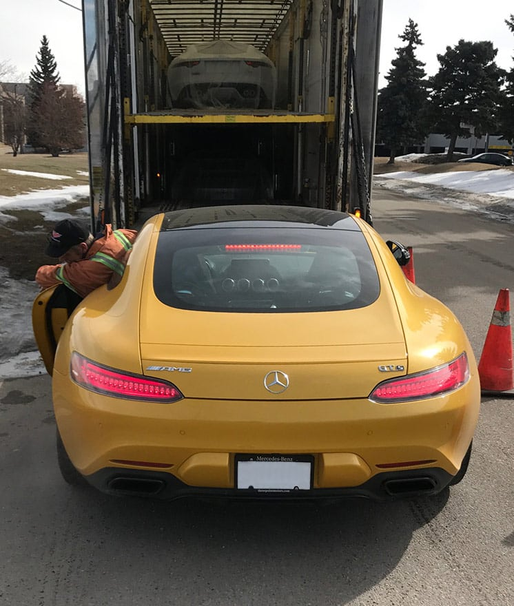 Mercedes-Benz AMG is carefully driven onto enclosed trailer hydraulic lift gate