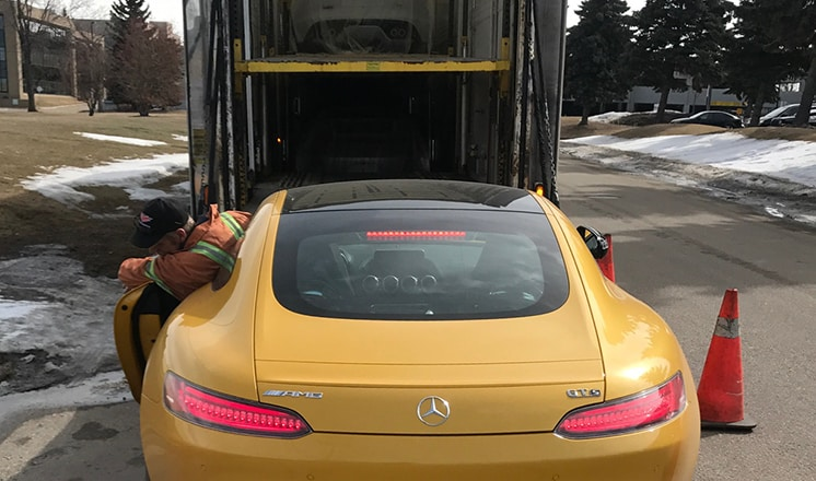 Mercedes-Benz AMG carefully driven onto enclosed trailer hydraulic lift gate