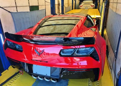 Red Corvette Z06 parked inside enclosed trailer