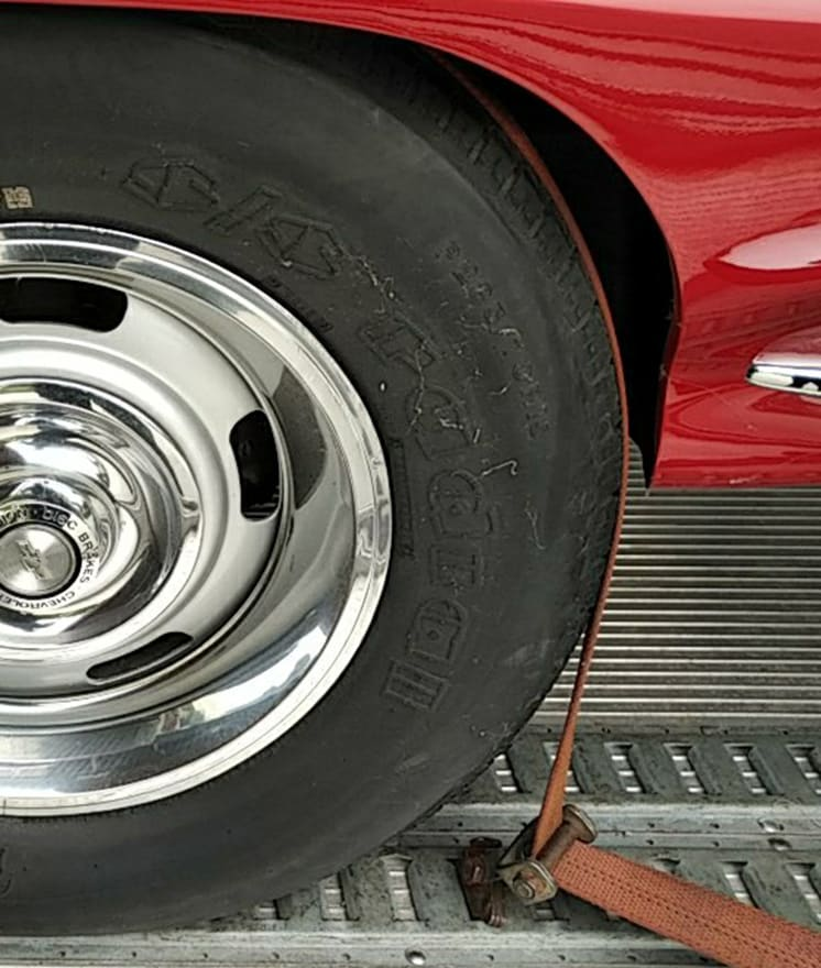Vehicles are secured with straps around wheel when transported via enclosed trailer