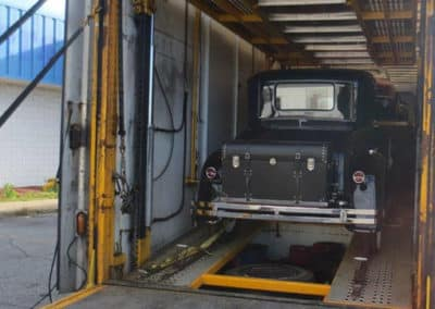 Vintage vehicle being unloaded from an enclosed trailer