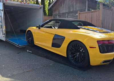 Yellow Audi R8 being loaded into enclosed trailer