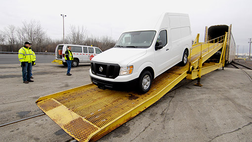 Van being driven down rail car ramp after transport