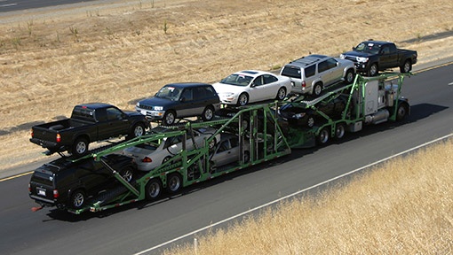 Open carrier transport truck shipping vehicles in prairies